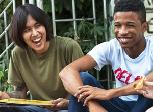 Two teens sitting and smiling.